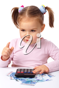 Royalty Free Photo of a Little Girl With a Calculator Counting Money and Pointing