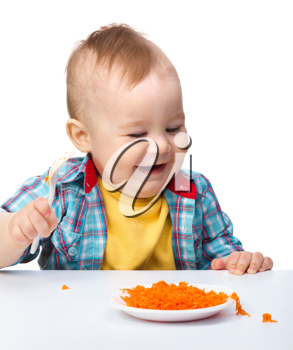 Royalty Free Photo of a Baby Eating Shredded Carrots