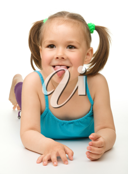 Royalty Free Photo of a Little Girl Lying on the Floor Sticking Her Tongue Out