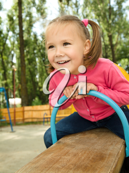 Royalty Free Photo of a Little Girl on a Teeter Totter