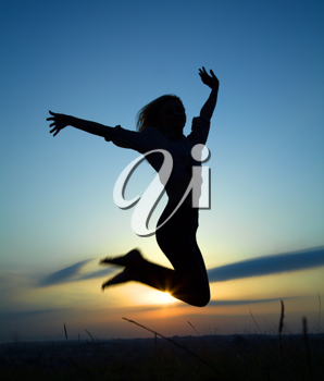 Royalty Free Photo of a Silhouette of a Woman Jumping in the Air