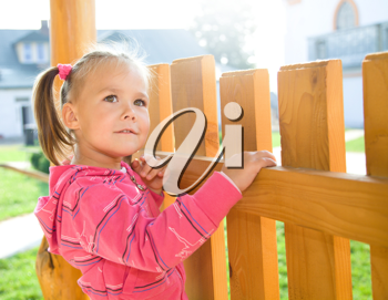 Royalty Free Photo of a Little Girl Standing in a Fence
