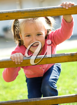 Royalty Free Photo of a Little Girl Climbing a Fence