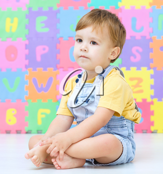 Portrait of a little boy sitting on floor