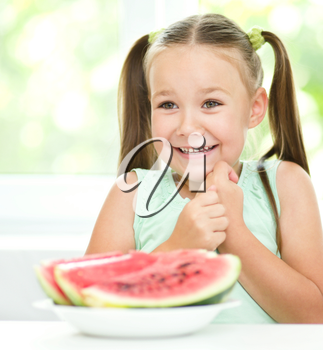 Cute little girl is eating watermelon, isolated over white