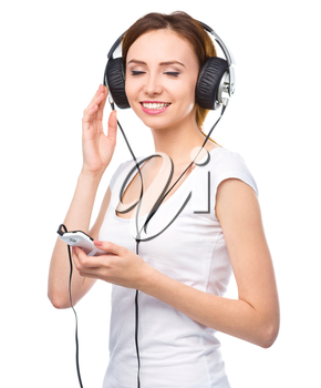 Closeup portrait of lovely young woman closing her eyes and enjoying music using headphones, isolated over white