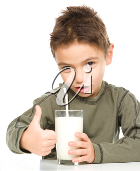 Cute boy drinks milk using a drinking straw while showing thumb up sign, isolated over white