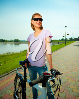 Young happy woman is standing behind bicycle, outdoor shoot
