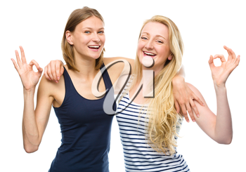 Two young happy women are hugging and showing OK sign, isolated over white