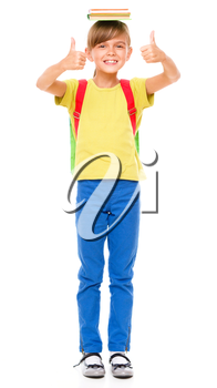 Portrait of a cute little schoolgirl with backpack holding book on her head and showing thumb up sign, isolated over white