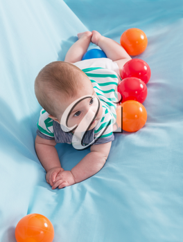 Adorable happy baby boy with multicolored balls on blue background