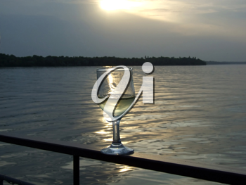 Royalty Free Photo of a Glass of Wine on a Railing at Sunset