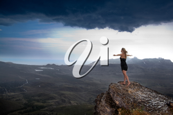 Royalty Free Photo of a Woman at the Edge of a Rock