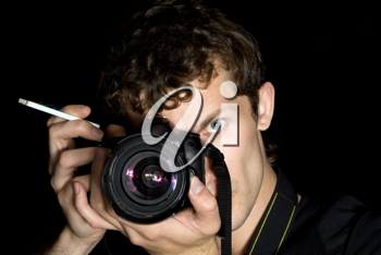 Royalty Free Photo of a Photographer Holding a Cigarette While Shooting a Picture