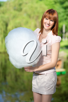 Smiling red-haired woman wearing short skirt and holding a cotton candy