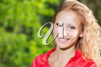 Portrait of smiling curly blond woman posing outdoors