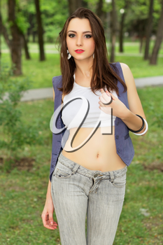 Young attractive woman posing in short top and jeans outdoors