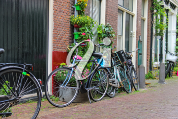 Parked bicycles near the brick house on the narrow street