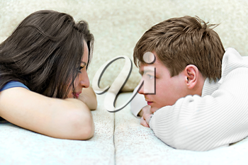 young boy and girl look at each other while lying on bed