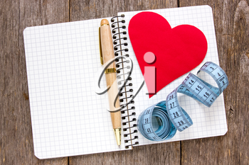 Royalty Free Photo of a Heart, Tape Measure and Pen on a Notebook