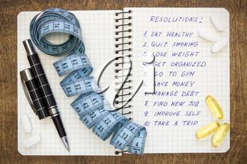 Resolutions written on a notepad with a measure tape and vitamin pills
