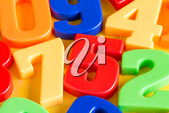 Colorful plastic numbers on a painted wooden background