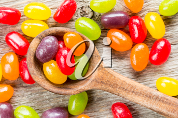 Spoon with colorful candies on the wooden background