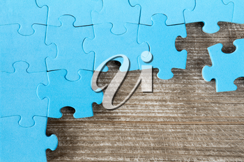 Blue puzzle on wooden background.Team business concept