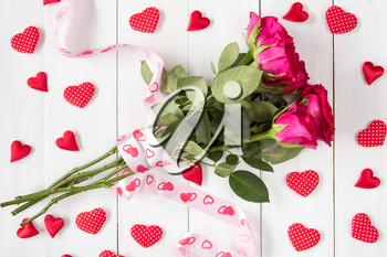 Bouquet of red roses with ribbon and many decorative hearts
