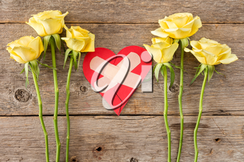 Human feeling repairing concept - red broken heart with yellow roses on wooden background