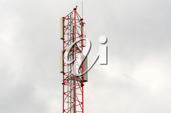Telecommunication tower on cloudy sky background