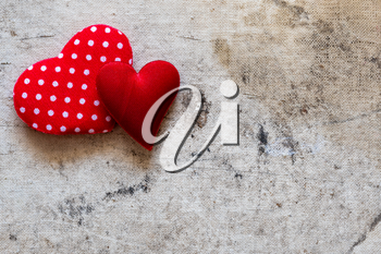 Two cute red hearts on the old canvas background. Copy space.