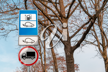 Electric car charging station road sign with trees background