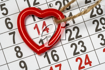 Memorable cute heart pendant on the February monthly calendar. Valentine's day background