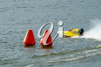 Yellow powerboat go fast along the lake and rounding a marker buoy in a race. Focus on orange buoy.