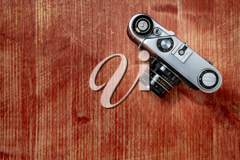 Old vintage camera on wooden background, top view, flat lay with copy space. Concept for the photographer, old photographic equipment, minimalistic style.