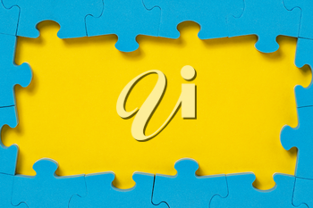 The frame from blue puzzle on yellow background with copy space