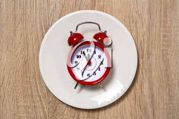 Plate with alarm clock with five minutes to twelve o'clock on the dial. Lunch time concept