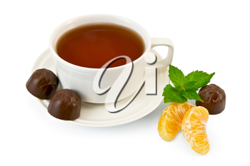 Tea in a white porcelain dish, three chocolates and two slices of mandarin, a sprig of green mint isolated on white background