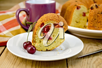 Cherry cake on a plate with cherry berries, napkin, knife, mug on the background of wooden boards