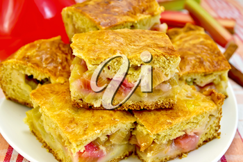 Chunks of sweet cake with rhubarb in a bowl, a jug of drink, rhubarb stalks, cinnamon on linen tablecloth background