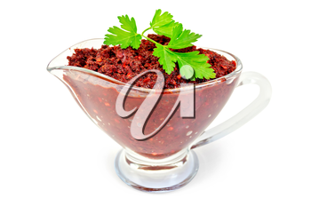 Tabasco adjika in a glass gravy boat with a sprig of parsley isolated on white background