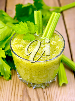 One glassful with a cocktail of celery and two petioles, stems and leaves of celery on a wooden boards background
