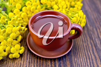 Herbal tea in a clay cup of fresh tansy flowers on the background of wooden boards