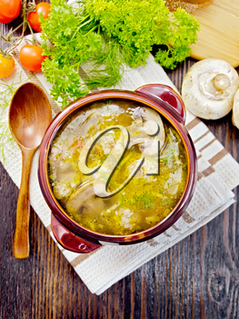 Soup with meatballs, noodles and champignon in a clay bowl on a napkin, parsley, tomatoes, mushrooms and bread on background a wooden board on top