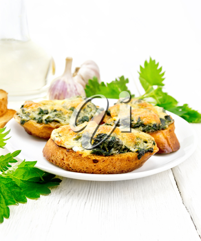Hot sandwiches with nettles and cheese on slices of wheat bread in a plate, garlic and vegetable oil on the background of a light wooden board