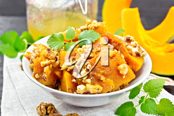 Pumpkin with walnuts and honey in a bowl on a towel, mint and fork on the background of wooden boards