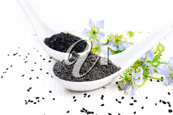 Flour and seeds of Nigella sativa in two spoons, sprigs of kalingini with blue flowers and green leaves on a wooden board background