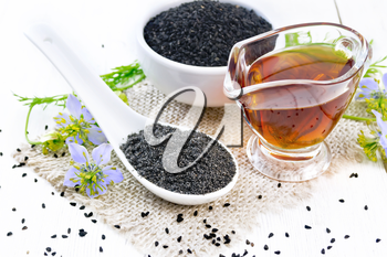 Flour Nigella sativa in a spoon, black cumin seeds in a bowl and oil in gravy boat on burlap, sprigs of kalingi with blue flowers and leaves on light wooden board background