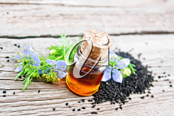 Nigella sativa oil in a bottle, seeds and twigs of black caraway seeds with blue flowers on a wooden board background